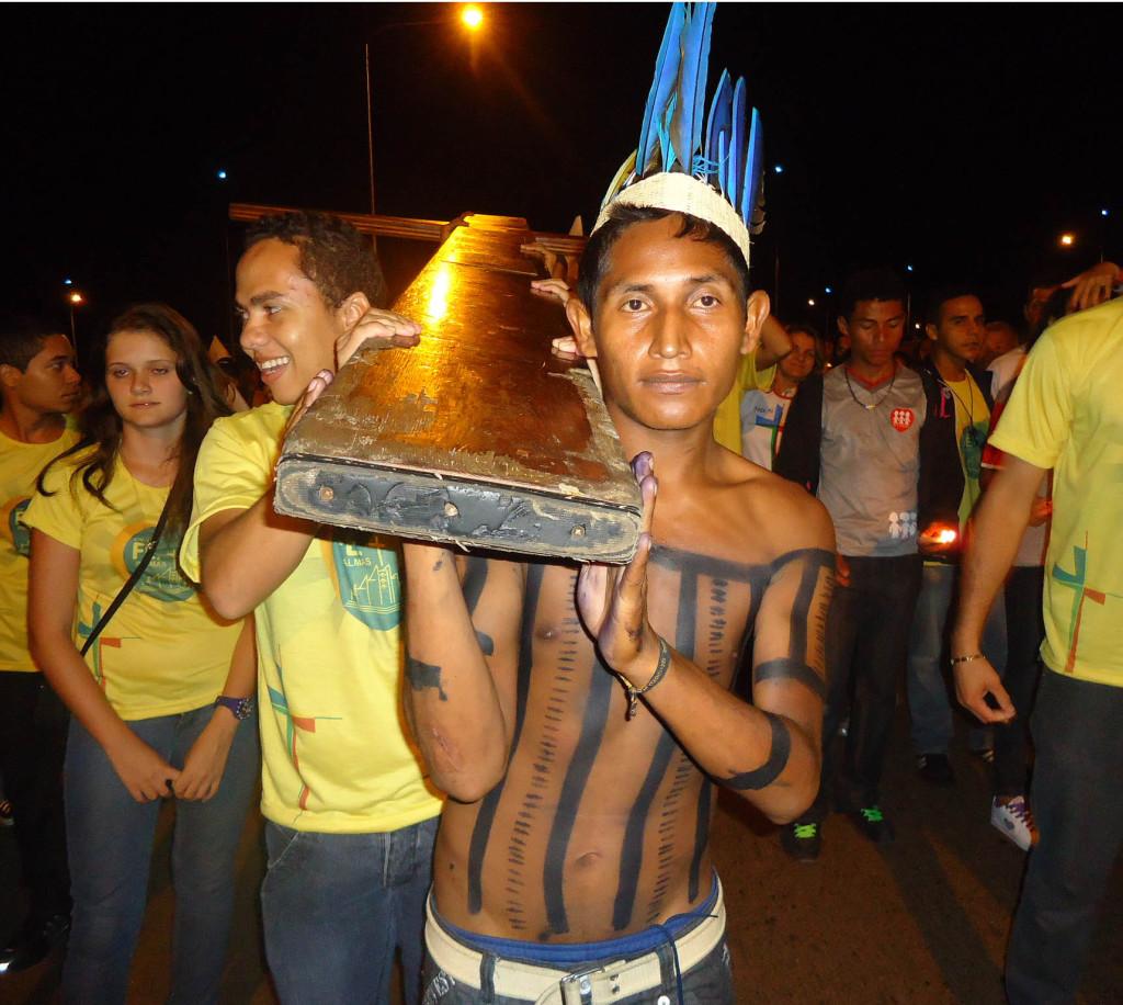 Jovem índio xerente ajuda a carregar a Cruz dos Jovens, no Bote Fé e Palmas (TO). Foto: Jovens Conectados.