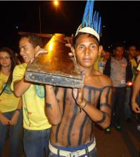 Jovem índio xerente ajuda a caregar a Cruz dos Jovens, no Bote Fé e Palmas (TO). Foto: Jovens Conectados.