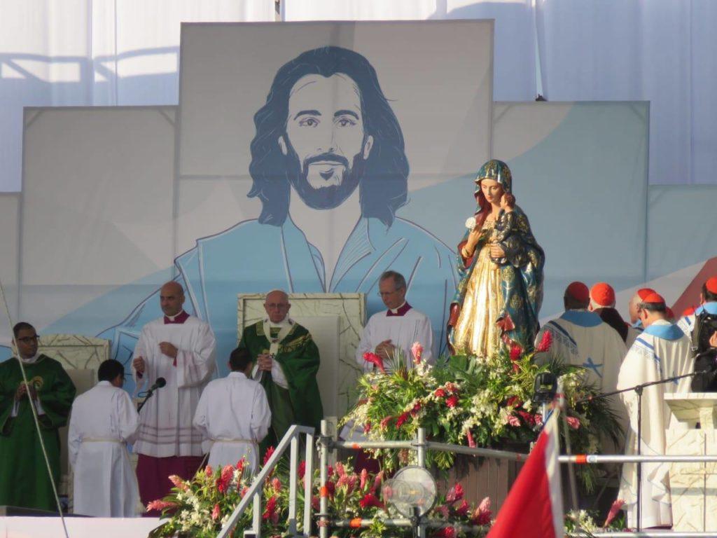 Papa Francisco em frente ao altar com a imagem de Jesus ao fundo e de Maria ao lado direito.