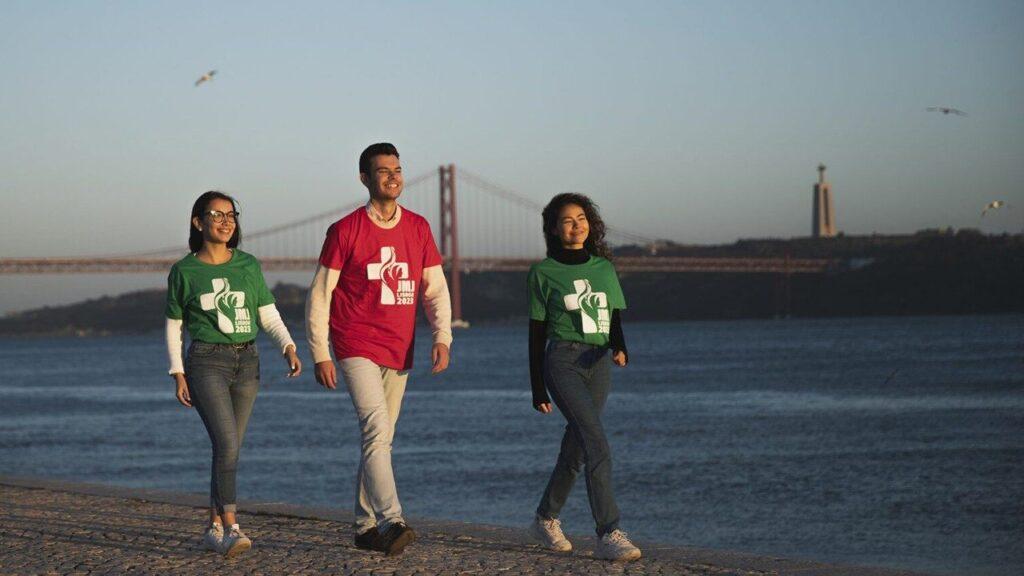 Para todo mundo ver: Três jovens (duas mulheres e um homem) com a camiseta da JMJ Lisboa 2023 andando em uma praia olhando para o horizonte em um fim de tarde, na imagem tem uma ponte ao fundo..